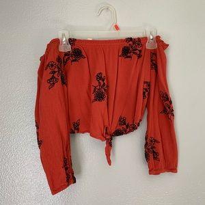 Red long sleeved crop top w black designs.